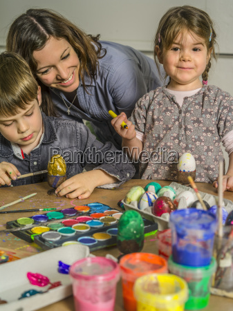 family decorating eggs for easter