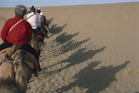 shadows of tourists on camels dunhuang