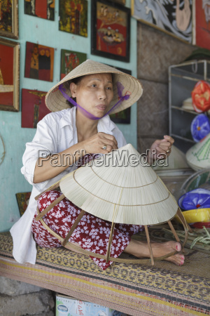 a women weaves a conical hat