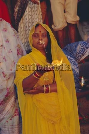 hindu woman pilgrim holding fire varanasi