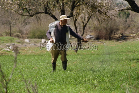 farmer spraying field on lasithi plateau