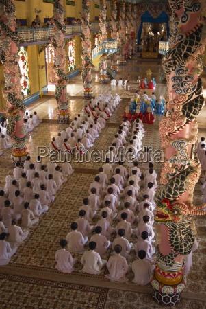 rows of monks at prayer inside