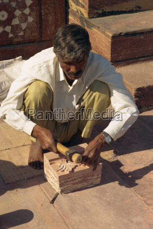 craftsman at work on stone carving