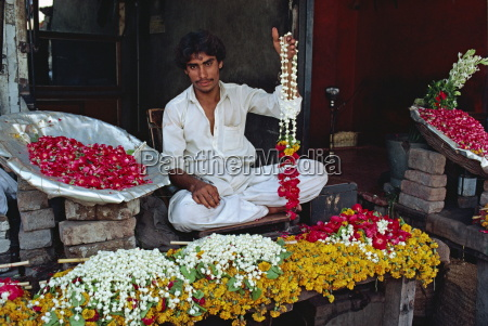 portrait of a man selling garlands