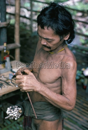 penan man making blowpipe darts mulu