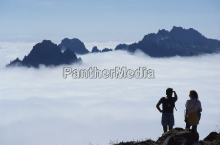 hikers look over the clouds from