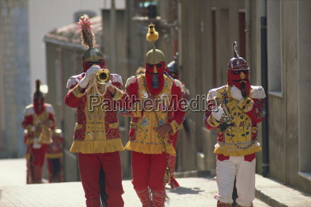trumpet players in red costumes and