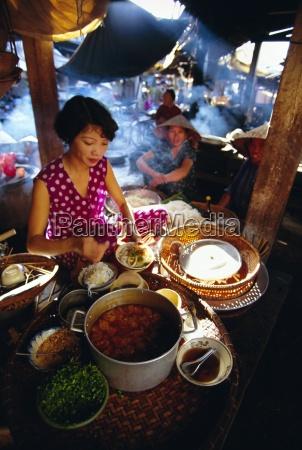 woman preparing food at a stall