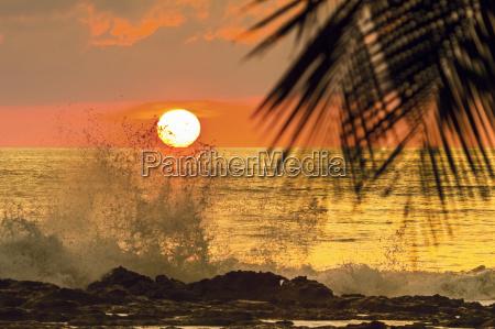 sun going down behind surf spray
