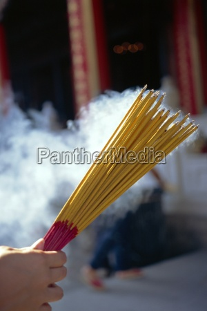 hand holding smoking incense sticks in