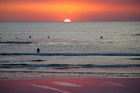 surfers and swimmers at sunset off