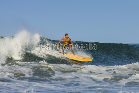 surfer on longboard riding wave at