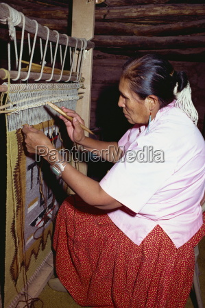 navajo indian woman weaving on a