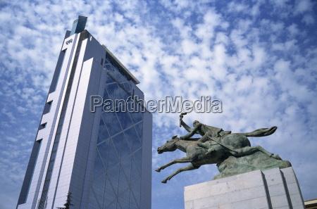 modern skyscraper and statue show contrast