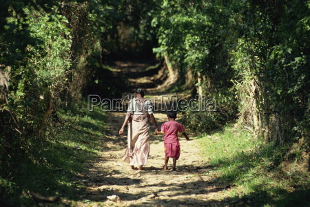 grandmother and child walking up leafy