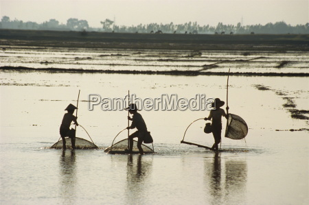 silhouettes of three fishermen in flooded