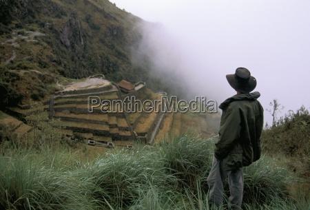 tourist watches clouds swirl around mountains