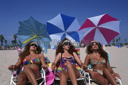 portrait of three women wearing sunglasses