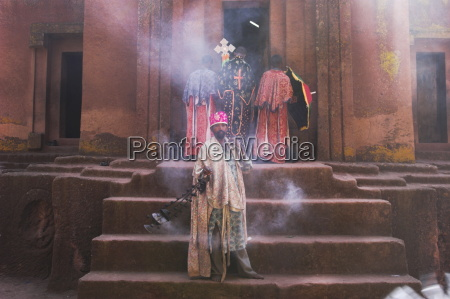 priest swings an incense burner at