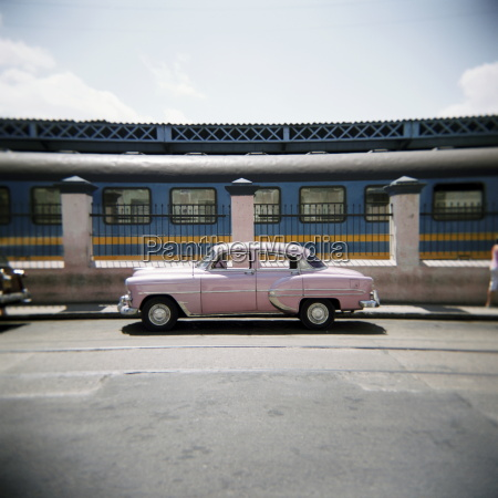old pink american car outside railway
