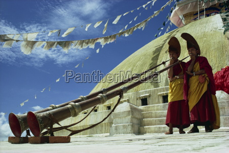 two monks blowing long horns nepal