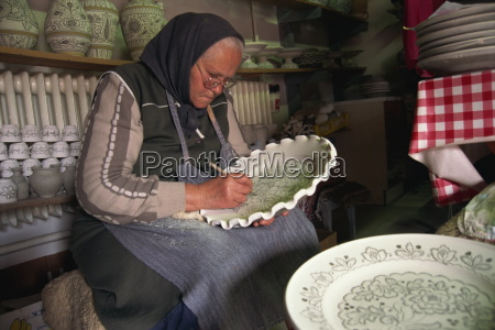 woman drawing design on a plate