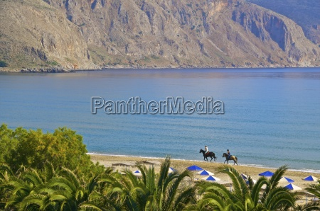 two tourists riding horses on the