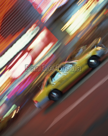 yellow cab driving past blurred neon