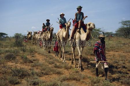 tourists on camels led by samburu