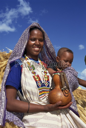 mother holding baby and gourd ethiopia