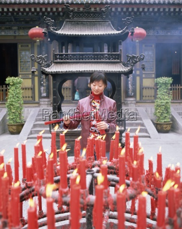 woman with candle and incense offerings