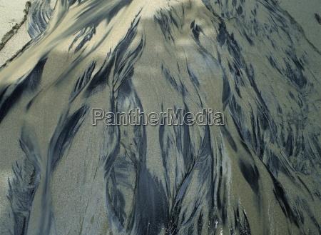 sand patterns in water dark volcanic