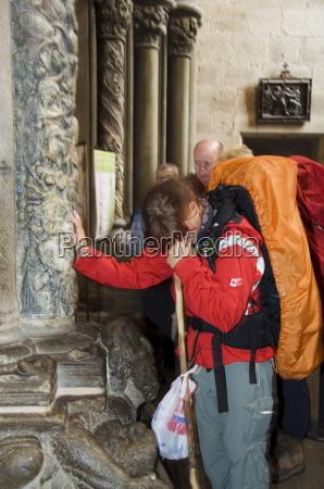 pilgrims touching a column on the