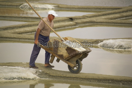 man pushing wheelbarrow in the salt