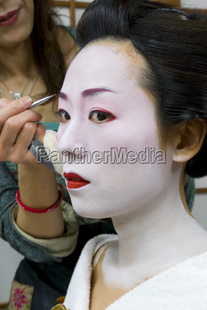 geisha having her make up applied