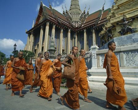monks in saffron robes walk past