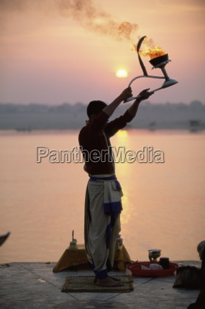 hindu man worshipping in front of