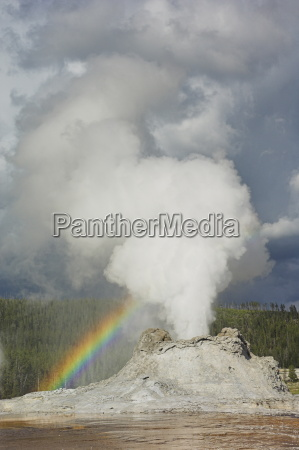 eruption of castle geyser with rainbow