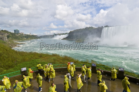 many tourists in yellow raincoats in