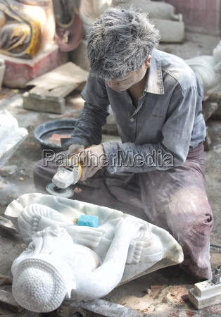 local man carving a marble buddha
