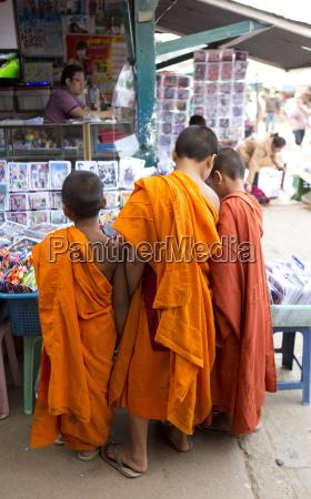 three novice monks buying comics in