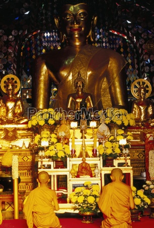 buddhist monks worshipping inside temple wat
