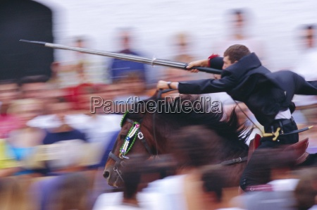 horse rider jousting with target during