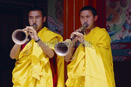 monks blowing flutes outside a gompa