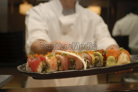 sushi chef presents a plate of