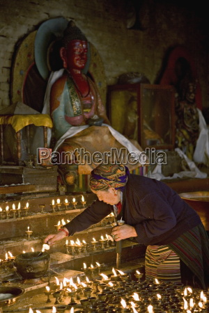 old woman lighting butter lamps in