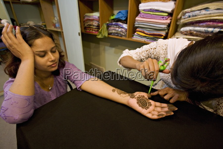 woman has henna design applied to
