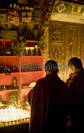 monks light butter lamps on an