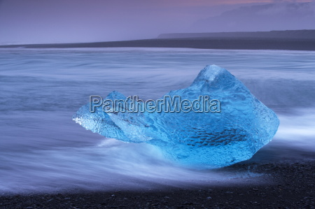 translucent blue iceberg washed ashore on