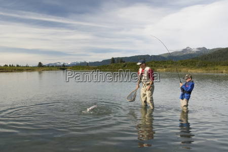boy catching a silver coho salmon